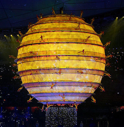 Illuminated Golden Sphere with dancers
